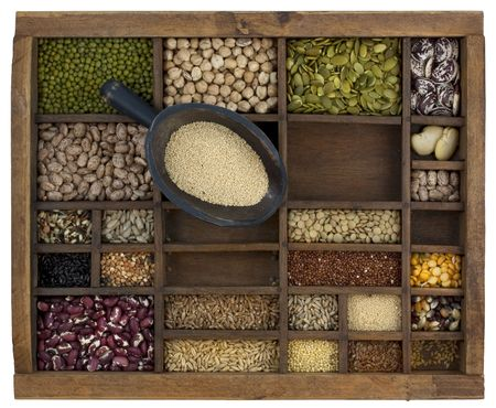 rustic scoop of amaranth grain and a variety of beans, lentils, seeds in old wooden typesetter case Stockfoto