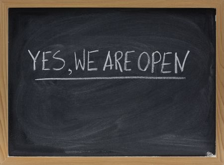 yes, we are open - business invitation handwritten with white chalk on blackboard with eraser smudges
