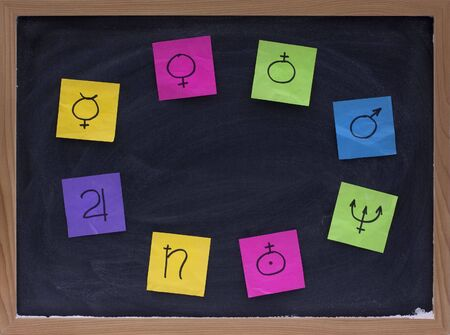uranus: blank copy space on blackboard surrounded by eight colorful sticky notes with astronomical signs for planets (Mercury, Venus, Earth, Mars, Jupiter, Saturn, Uranus, Neptune)