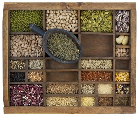 typesetter: rustic scoop of French green lentils and a variety of beans, lentils, seeds in old wooden typesetter case, isolated with path