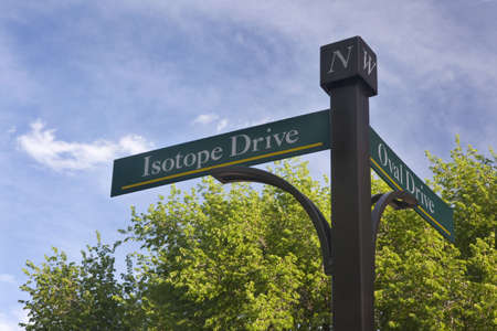 isotope: Isotope and Oval Drive - street sign on Colrado State University Campus at Fort Collins against blue sky and fresh green tree leaves