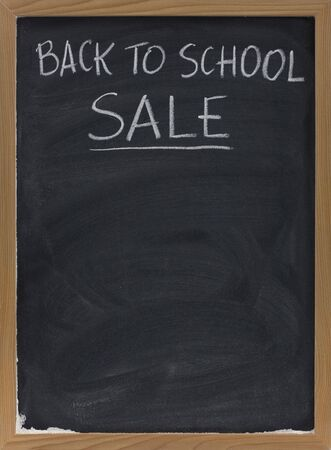 back to school sale advertisement handwritten with white chalk on a blackboard with eraser smudges, copy space below Stock Photo - 4928797
