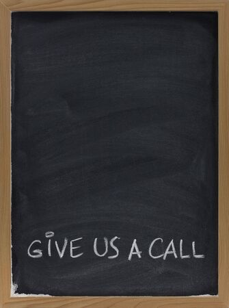 give us a call advertisement handwritten with white chalk on blackboard, copy space above Stock Photo - 4928798