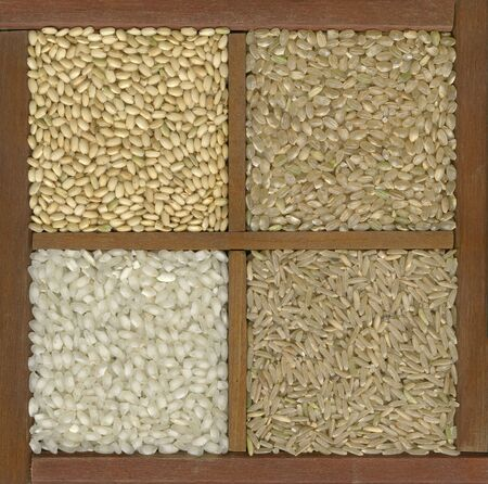 clockwise: four rice grains in a primitive wooden box or drawer with dividers - left bottom white arborio (risotto) and, clockwise, three brown varieties: sweet (sushi), short, long grain