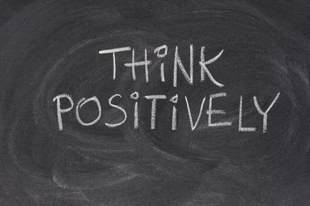 smudges: think positively slogan handwritten with white chalk on blackboard with strong eraser smudges