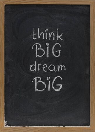 slogan: pensar en grande, so�ar en grande con el lema de mano de color blanco tiza en la pizarra con borrar manchas
