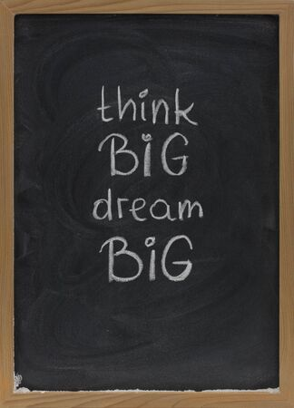 think big, dream big slogan handwritten with white chalk on blackboard with erase smudges
