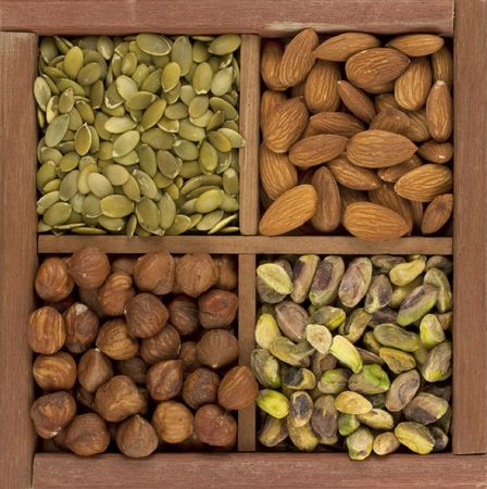 four healthy raw snacks, almonds, hazelnuts, pistachio nuts and pumpkin seed, in a rustic wooden box or drawer with dividers