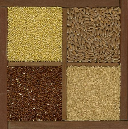 cereal box: four ancient cereal grains - millet, spelt, amaranth, red quinoa in a wooden box or drawer with dividers Stock Photo