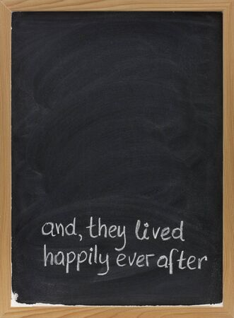 narrative: and, they lived happily ever after -  stock phrase for ending oral narratives or fairytale handwritten with white chalk on blackboard, copy space above Stock Photo