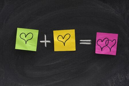 interlaced: love or romantic relationship concept presented as mathematical equation with hearts, colorful sticky notes, white chalk on blackboard Stock Photo