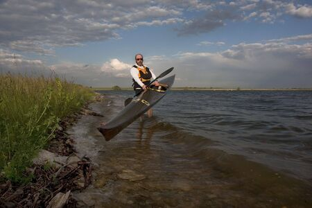 paddler: mature paddler launching long racing carbon fiber kayak on a lake with grassy and rocky shore in northern Colorado, thirteen - temporary race number placed on deck by myself