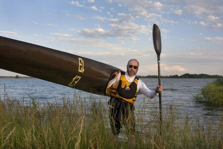 paddler: mature paddler carrying his long racing kayak on a grassy lake shore in northern Colorado, thirteen - temporary race number placed on deck by myself