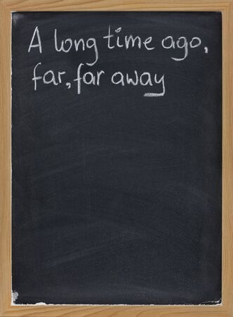 narratives: A long time ago, far, far away - a phrase for opening oral narratives, story or fairytale handwritten with white chalk on blackboard, copy space below