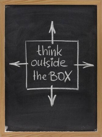denken buiten de box - concept van verschillende of onconventioneel denken geschetst met wit krijt op een schoolbord met gum vlekken Stockfoto