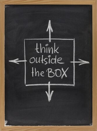 is creative: think outside the box - concept of different or unconventional thinking sketched with white chalk on a blackboard with eraser smudges