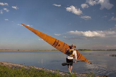 mature paddler in a hat and life jacket carrying his home built wooden sea kayak after paddling workout, grassy lake shore in northern Colorado Stock Photo - 5204502