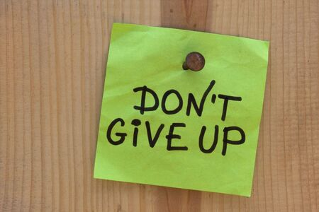 not give: do not give up  - motivational reminder on post note nailed to wooden plank or wall