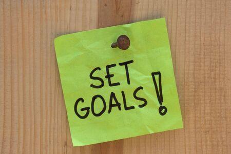 note of exclamation: Establezca metas - Recuperaci�n de motivaci�n en el post nota clavada en tabl�n de madera o de la pared Foto de archivo