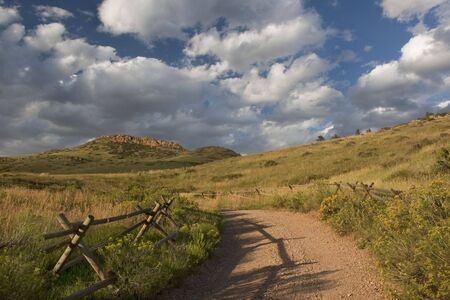 dirt road and wooden fence at foothills of Rocky Mountains near Fort Collins, Colorado, late summer Stock Photo - 5411687