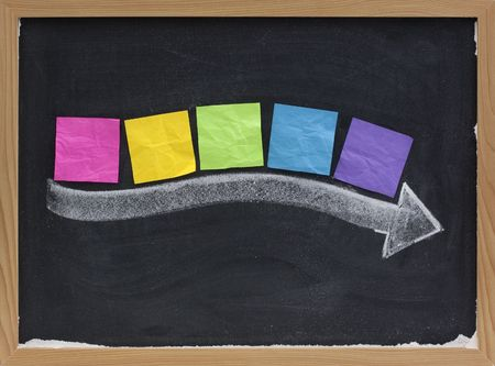timeline concept - blank colorful sticky notes along thick white chalk arrow on blackboard with copy space