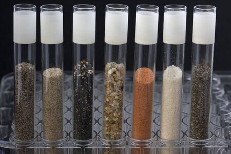 science abstract - glass testing tubes with different sand samples collected from beaches and deserts of western USA and Hawaii Stok Fotoğraf