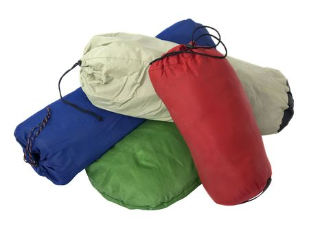 a pile of colorful bags with camping equipment (tent, sleeping bag, pad) isolated on white