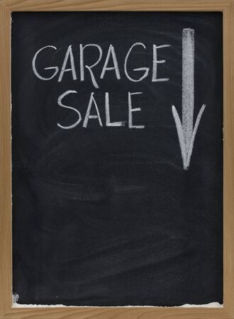 garage sale text handwritten with white chalk on vertical blackboard with arrow and copy space below photo