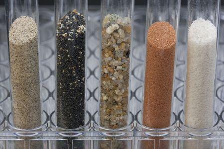 cinque tubi prove di vetro con diversi campioni di sabbia raccolti da spiagge e deserti occidentali di Stati Uniti e Hawaii Archivio Fotografico