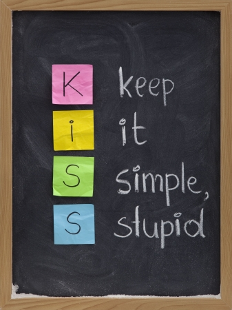 KISS keep it simple, stupid - design principle presented with sticky notes and white chalk handwriting on blackboard Foto de archivo