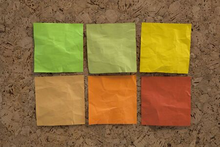 six blank crumpled sticky notes in earth colors (green, brown, yellow) on a cork bulletin board Stock Photo - 5668581