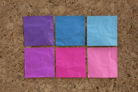 six blank crumpled sticky notes in blue, pink, magenta colors on a cork bulletin board photo
