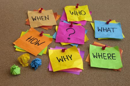 when: who, what, where, when, why, how questions - uncertrainty, brainstorming or decision making concept, colorful crumpled sticky notes on cork bulletin board
