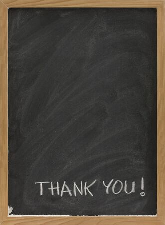 smudges: thank you handwritten with white chalk on blank blackboard with eraser smudges