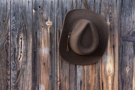 cappello cowboy: lana di feltro marrone cappello da cowboy in pelle fascia appeso al muro in legno stagionato di vecchio fienile