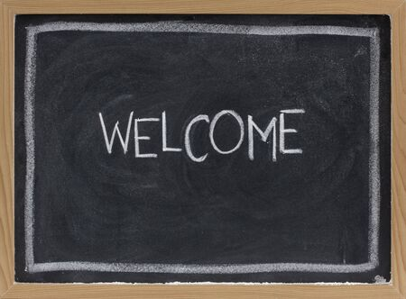 smudge: welcome - white chalk handwriting on blackboard with eraser smudge texture Stock Photo
