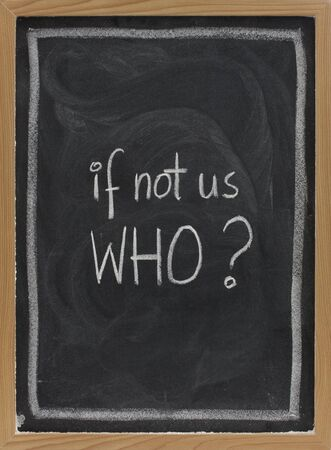 smudge: if not us, who - question handwritten with white chalk on blackboard, eraser smudge patterns Stock Photo