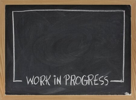 work in progress text in white chalk handwriting, rectangular frame on blackboard with eraser smudge patterns and blank copy space Stock Photo