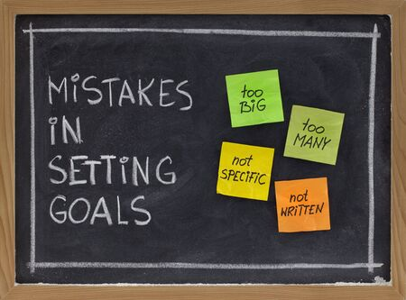 common mistakes in setting goals (too many, too big, not specific, not written) - concept presented with sticky notes and white chalk handwriting on blackboard