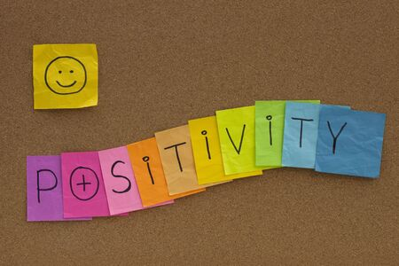 positivity concept on cork bulletin board - colorful sticky notes with a smiley