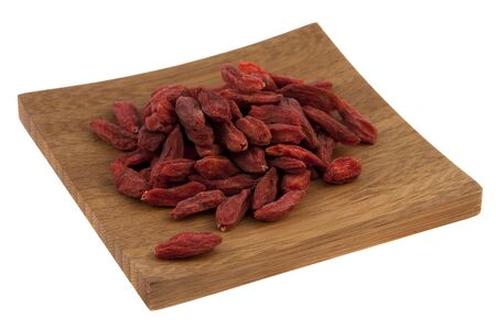 a pile of dried Tibetan goji berries (wolfberry) on a small wooden square tray isolated on white, selected focus on fruits photo