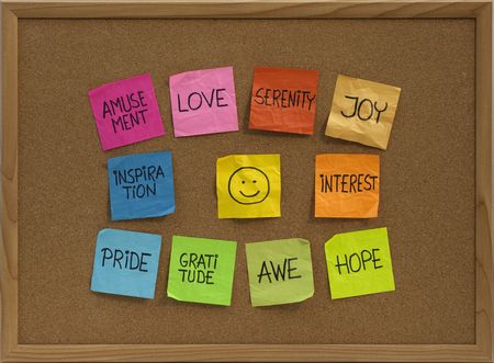 positive emotions concept - color sticky notes around smiley on cork bulletin board photo