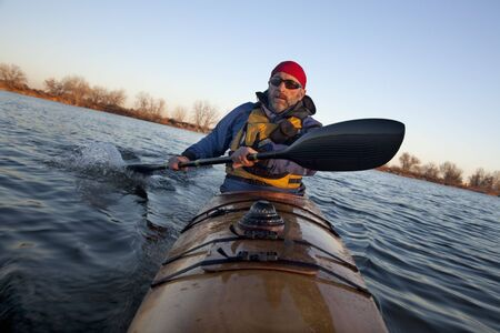 paddler: mature male paddler exercising (turning boat using rudder stroke with his wing carbon fiber paddle) in a home built wooden sea kayak on lake, fall scenery  in Colorado, view from kayak bow