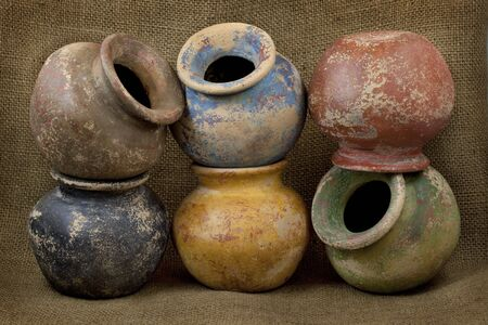 jardineras: seis vasijas de arcilla de peque�a planta (masa producidos plantadores) con color de �spera terminar sobre fondo de textura de arpillera oscuro, bodeg�n Foto de archivo