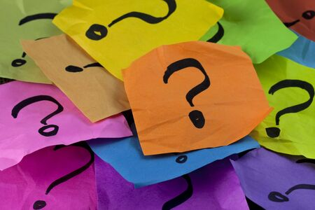 unsure: questions, decision making or uncertainty concept - a pile of colorful crumpled sticky notes with question marks