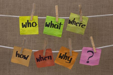 when: who, what, where, when, why, how questions - uncertainty, brainstorming or decision making concept, colorful crumpled sticky notes hanging on clothesline against canvas background Stock Photo