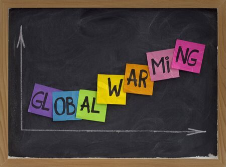 global warming concept - colorful sticky notes and white chalk drawing on blackboard Stock Photo