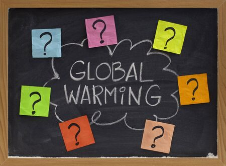 noted: concept of global warming question - doubt or unsolved problems, white chalk handwriting and colorful sticky noted on blackboard