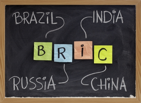 emerging markets: BRIC (Brazil, Russia, India, China) acronym - emerging markets or new economies, white chalk handwriting, colorful sticky notes on blackboard
