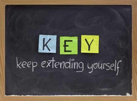 self development: KEY (keep extending yourself) - coaching, motivational, self development acronym, white chalk handwriting and colorful sticky notes on blackboard Stock Photo